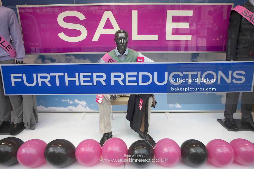 Shop window mannequins and banners for Sale and further redictions in the wide window pane of Austin Reed in London's regent Street, England.