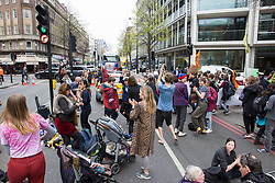 London, UK. 16th April 2019. Climate campaigners from Extinction Rebellion start to dance in Edgware Road as a police officer tries to obtain identification details from a man who had been praying at a religious service in the road during the second day of International Rebellion UK activities by climate campaigners from Extinction Rebellion to call on the Government to take urgent action to address climate change.