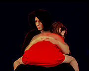 Mother and daughter daugter sitting on mothers lap with her back to camera black background dreamy atmosphere