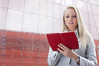 Beautiful young businesswoman reading notes in organizer while standing against office building