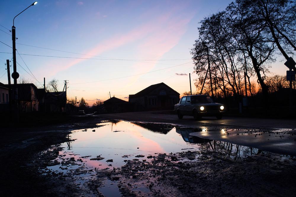 Une voiture dans les rues de Hlukhiv au coucher du soleil, 7 d&eacute;cembre 2015. <br /> <br /> A car drives past a puddle as the sun sets on December 7, 2015on the outskirts of Hlukhiv, Ukraine.