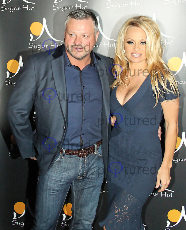 Sugar Hut owner Mick Norcross poses with Pamela Anderson, London, UK. April 20, 2012. (Photo by Brett Cove)