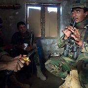 A Afghan soldier plays a flute while others peel potatoes on the front lines in the Howz-E-Madad area a day before a joint operation against Taliban insurgents with Canadian Forces in Zharay District, Kandahar Afghanistan which along with nearby Panjwa'i are the most volatile areas in the country and the scene of heavy fighting with Taliban insurgents up through 2010, which has become the site of some of the largest land battles in NATO's history.<br /> &copy; Louie Palu/ZUMA Press/New America Foundation