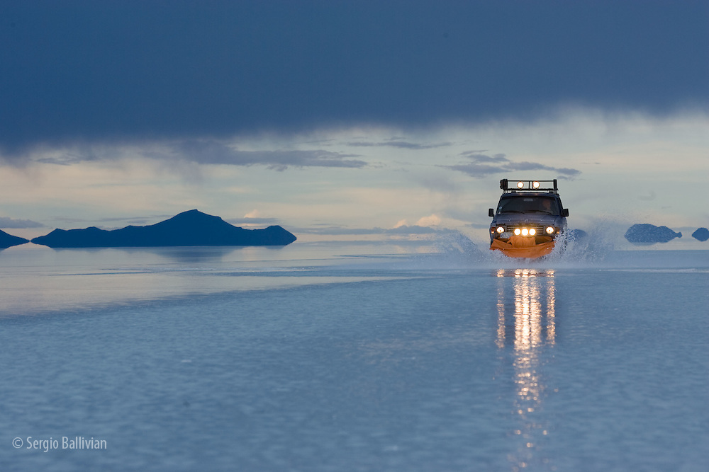 Travelers drive their SUV across the Salar de Uyuni, a flooded salt flat, in Bolivia