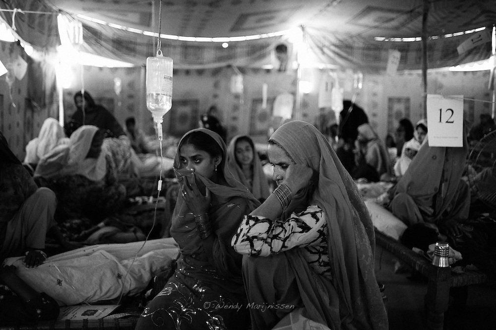 Family members surround the bed of a woman who was just brought back to the makeshift patient ward on the rooftop of the Dr. Hassan Medical Centre. Kandiaro, Pakistan, 2010