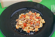 gramigna pasta, handmade with traditional press called torchio with sausage sauce on black dish close-up from above, italian traditional food of Modena
