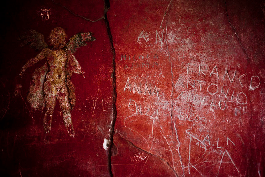 Tourists's writings damages on Thermopolium of Vetutius Placidus frescos in Pompeii. Nearly 4 month after the collapse of the House of the Gladiators and then of a wall at the House of the Moralist, Pompeii still faces neglet and mismanagement.Now the Italian government has begun to investigate the matter. Nine people are to be questioned, although Marcello Fiori, the emergency commissioner who was appointed to save the site in 2008, is conspicuously absent from the group.Those who will be grilled by the public prosecutor include the former superintendent of Naples and Pompeii, the site director who oversaw the waterproofing of the House of the Gladiators, the head of technical services at Pompeii, and an architect. The investigation will also examine Fiori's administration, which ended in July, including its use of government funds, which many critics have seen as wasteful and ineffective.