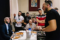 """NAPLES, ITALY - 30 JULY 2018: Roberto Saviano (left), an Italian journalist, writer and essayist chats with the young actors and organisers of the collective """"Nuovo Teatro Sanità"""" (New Sanità Theatre) during lunch in the Sanità neighborhood in Naples, Italy, on July 30th 2018.<br /> <br /> In 2017 the 17-year-old innocent victim Genny Cesarano was shot and killed by stray bullet  in cross fire between 2 rival gangs vying for territorial control in the Sanità neighborhood.<br /> The  isolation of the neighborhood Sanità over the years provided an ideal location for the Camorra to expand their illicit activities and profit from soaring unemployment rates and economic instability,<br /> <br /> After the first death threats of 2006 by the Casalese clan , a cartel of the Camorra, which he denounced in his exposé and in the piazza of Casal di Principe during a demonstration in defense of legality, Roberto Saviano was put under a strict security protocol. Since 2006 Roberto Saviano has lived under police protection.<br /> <br /> Saviano's latest novel """"The Piranhas"""", which tells the story of the rise of  a paranza (or Children's gang) and it leader Nicolas, will be released in the United States on September 4th 2018."""