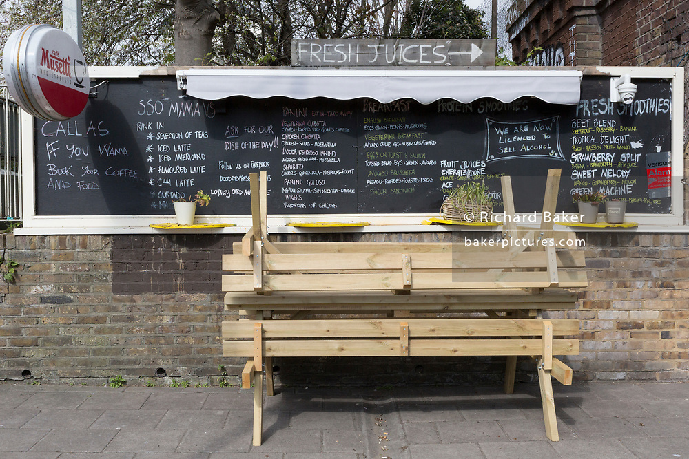 As the second week of the Coronavirus lockdown continues around the capital, and the UK death toll rising by 563 to 2,325, with 800,000 reported cases of Covid-19 worldwide, in accordance with the government's forced lockdown and closure of businesses, benches are upturned in front of daily menu for drinks and food snacks outside a cafe near the local Overground station on Clapham High Street, on 1st April 2020, in south London, England.