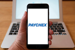 Using iPhone smartphone to display logo of Paychex the American provider of payroll, human resource, and benefits outsourcing services for businesses.