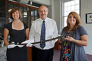 Stephanie Ruth, right, donates sword to Athens Historical Society to Executive Director Ron Luce, center, and Curator Jessica Cyders, left.