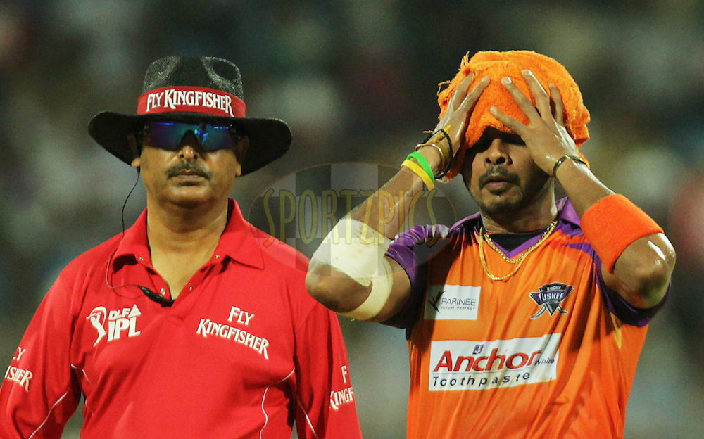Umpire S Asnani watches S Sreesanth of Kochi Tuskers Kerala wipe his face during  match 10 of the Indian Premier League ( IPL ) Season 4 between the Pune Warriors and the Kochi Tuskers Kerala held at the Dr DY Patil Sports Academy, Mumbai India on the 13th April 2011..Photo by BCCI/SPORTZPICS