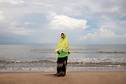Rokeeyoh Sana-Ae stands on the beach located next to her community in the Tae Pa District of Songklah Province. Where she stands is the proposed site for a coal-powered power plant which the community vigorously opposes saying it will destroy the natural habitat of the area and their community.