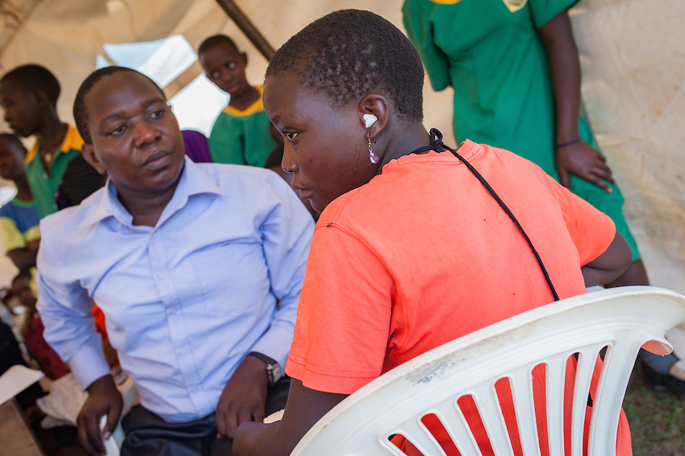 CAPTION: Sumaya has her ears checked and cleaned free of charge at an event run by SignHealth Uganda at Kakunyu Inclusive Nursery and Primary School in the village of Kakunyu. On these occasions, SignHealth runs cultural shows and musical performances alongside the ear screenings and HIV tests it offers in order to attract more participants. The dramas that are staged often try to describe scenarios wherein hearing impaired people express the challenges and the discrimination they face owing to their condition. LOCATION: Kakunyu Inclusive Nursery and Primary School, Kakunyu Village, near Masaka city, Lweongo District, Central Region, Uganda. INDIVIDUAL(S) PHOTOGRAPHED: Left: Sumaya Nabulya; right: Michael Nsanze Makumbi.