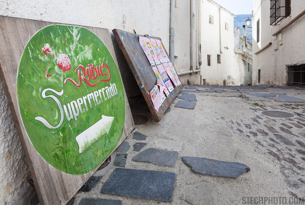 A supermarket (supermercardo) sign on the side of a road in the town of Alpujarra de la Sierra, Almeria, Andalucia, Spain.
