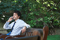 Businessman sitting on park bench talking on cell phone