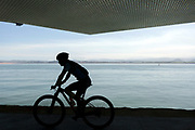 SANTANDER, SPAIN - April 17 2018 - Cyclist riding past the Botin Centre along Santander seafront with view looking out to Somo, Cantabria, Northern Spain, Europe.