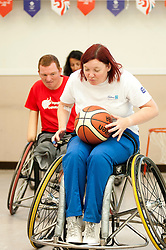 Cadbury 2012 Paralympic demonstration Sheffield..Kathryn Betts (London 2012 Site Ambassador for Sheffield) tries her hand at wheelchair basketball hotly pursued down the court by coach Andy Atkinson who was on site with the  RGK Rhinos Sporting club wheelchair basketball team to give Sheffield colleagues an insight into Wheelchair basketball, Paralympic sports and promote awareness around the different sporting disciplines.   .  ....3 September 2012.Image © Paul David Drabble