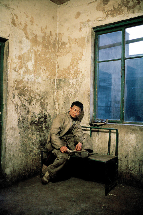 Worker at a coking plant having a short break during his shift. On average these workers earn approximately 1000RMB (100 Euro) per month, on a normal week they work 8 hour shifts for everyday of the week. Benxi, China. 2007