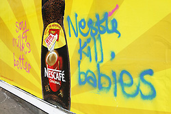 Billboard advertising powdered baby milk with graffiti on it protesting against the company breaking the world health Organisation Code on the marketing of breast milk substitutes,