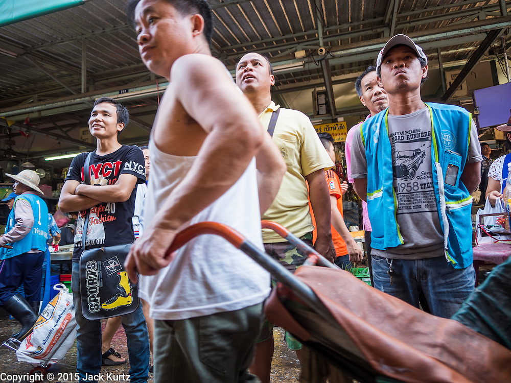 """12 JUNE 2015 - BANGKOK, THAILAND: Thais watch the Thai women's football (soccer) team play in the Women's World Cup on television on a TV hanging in Khlong Toey Market. Khlong Toey (also called Khlong Toei) Market is one of the largest """"wet markets"""" in Thailand. The market is located in the midst of one of Bangkok's largest slum areas and close to the city's original deep water port. Thousands of people live in the neighboring slum area. Thousands more shop in the sprawling market for fresh fruits and vegetables as well meat, fish and poultry.          PHOTO BY JACK KURTZ"""