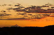 """The volcanic cone of Mount Egmont / Taranaki (2518 meters or 8261 feet) rises in Mount Egmont National Park and glows at sunset, seen from Tongariro in New Zealand, North Island. Taranaki was a stand-in for Mount Fuji in the Tom Cruise motion picture, """"The Last Samurai""""."""