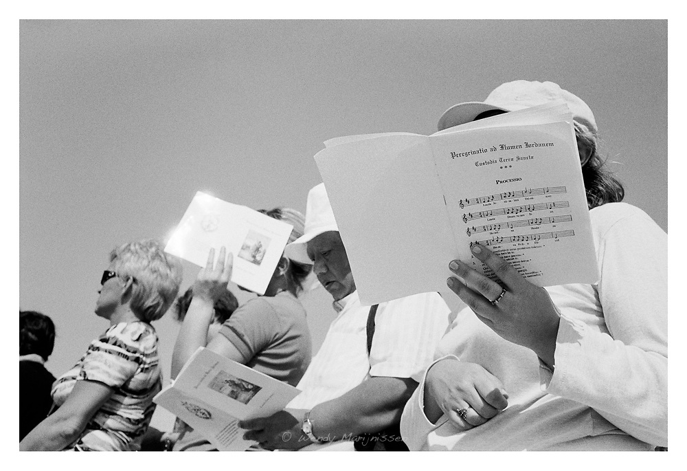 Religious tourists singing during a church service outside in the Jordanian valley. Israel, 2006