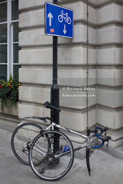 A bicycle has been dismantled, its front wheel detached from the frame on a City of London street sign post where arrows point up and down, the coincidence of a visual pun - in the heart of the capital's financial district. The authorities recommend locking up a bike in specified areas, making sure they're secured with a substantial D-lock. The bike is a Canondale road bike of a single-gear variety..