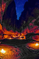 Candles illuminate the path at night in The Siq, the 1200 meter long gorge that leads into the Petra Archaeological Park, Jordan.