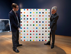 © Licensed to London News Pictures. 05/10/2012. LONDON, UK. Members of Christie's staff hold Damien Hirst's 'Anhydrogitalin' (1993) estimated to fetch GB£500,000-700,000 at an auction preview in London today (05/10/12). The evening auction, consisting of post-war and contemporary art, takes place at Christie's St James' auction house on the 11 October 2012. Photo credit: Matt Cetti-Roberts/LNP