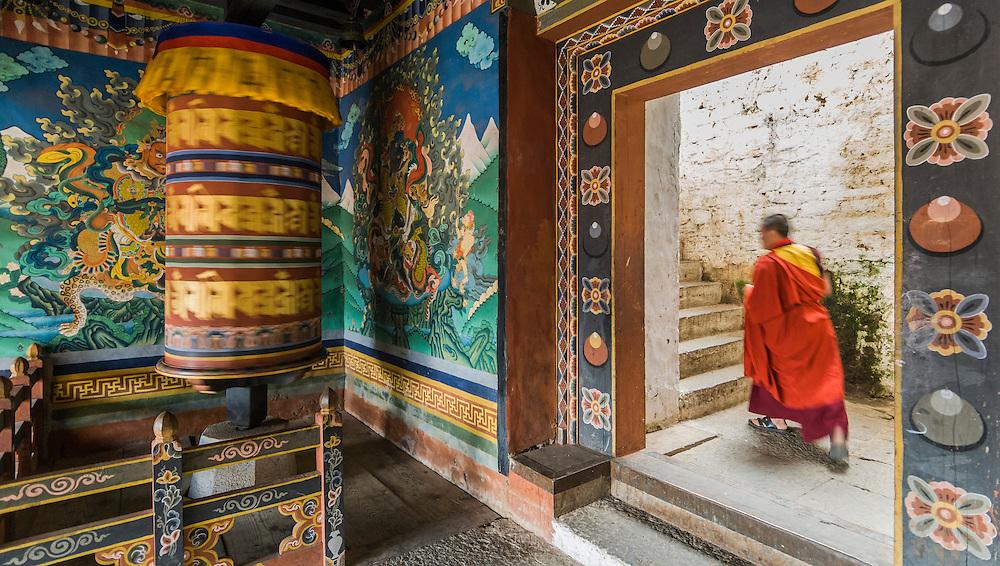 Bhutan, Trongsa Dzong, large prayer wheel and monk waliking upstairs