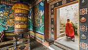 Bhutan, Trongsa Dzong, large prayer wheel and monk waliking upstairs