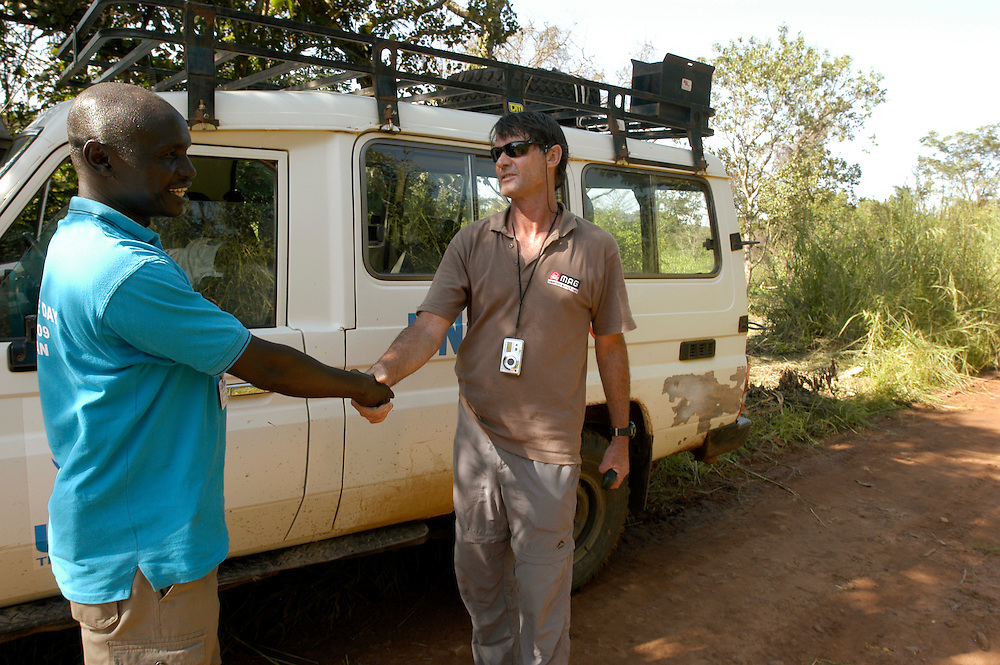 Steph Naude, a Technical Field Manager for Mines Advisory Group (MAG), consults with Joseph Guya, a representative of the United Nations High Commissioner for Refugees (UNHCR) about the clearence of a detour route that would allow the UNHCR to repair a bridge over the Aisa River necessary for the transport of food to refugee camps in Central Equatoria province..Mitika, South Sudan. 30/09/2009..Photo © J.B. Russell