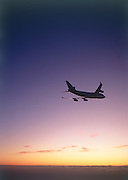 Wide body airplane flying into sunset