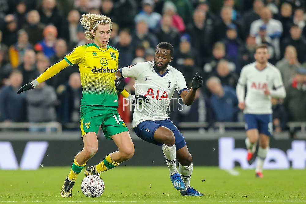 Tottenham Hotspur midfielder Tanguy NDombèlé (28) battles for possession with Norwich City midfielder Todd Cantwell (14) during The FA Cup match between Tottenham Hotspur and Norwich City at Tottenham Hotspur Stadium, London, United Kingdom on 4 March 2020.