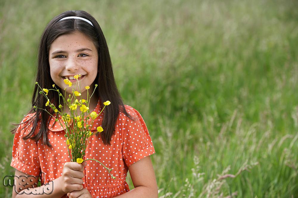 Girl (7-9) holding flowers in field portrait