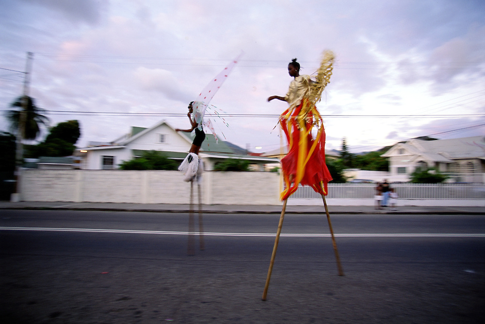 "Trinidad and Tobago ""MOKO JUMBIES: The Dancing Spirits of Trinidad"".(Two children from the 'South Moko Jumbies' seem to fly down a wide street in Port of Spain.).A photo essay about a stilt walking school in Cocorite, Trinidad..Dragon Glen de Souza founded the Keylemanjahro School of Art & Culture in 1986. The main purpose of the school is to keep children off the streets and away from drugs..He first taught dances like the Calypso, African dance and the jig with his former partner Cathy Ann Samuel.  Searching for other activities to engage the children in, he rediscovered the art of stilt-walking, a tradition known in West Africa as the Moko Jumbies , protectors of the villages and participants in religious ceremonies. The art was brought to Trinidad by the slave trade and soon forgotten..Today Dragon's school has over 100 members from age 4 and up..His 2 year old son Mutawakkil is probably the youngest Moko Jumbie ever. The stilts are made by Dragon and his students and can be as high as 12-15 feet. The children show their artistic talents mostly at the annual Carnival, which today is unthinkable without the presence of the Moko Jumbies. A band can have up to 80 children on stilts and they have won many of the prestigious prizes and trophies that are awarded by the National Carnival Commission. Designers like  Peter Minshall , Brian Mac Farlane and Laura Anderson Barbata create dazzling costumes for the school which are admired by thousands of  spectators. Besides stilt-walking the children learn the limbo dance, drumming, fire blowing and how to ride  unicycles..The school is situated in Cocorite, a suburb of Port of Spain, the capital of Trinidad and Tobago..all images © Stefan Falke"