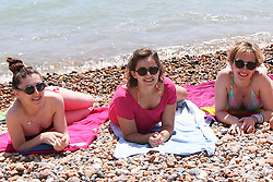 © Licensed to London News Pictures. 16/07/2014. Brighton, UK. A group of women relaxing and sunbathing on Brighton beach at lunchtime. Temperatures in parts of the south east are expected to hit 30 degrees this week. Photo credit : Hugo Michiels/LNP