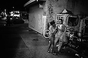 Two girls talk and eat popcorn as they stop along Broadway in Bushwick, NY.