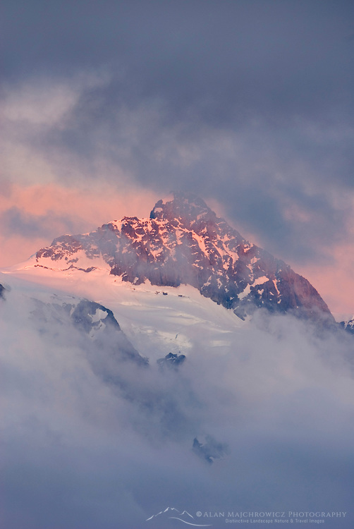 Summit of Mount Shuksan 9,127 feet (2,782 metres) seen through clearing storm clouds at sunset. North Cascades National Park Washington USA