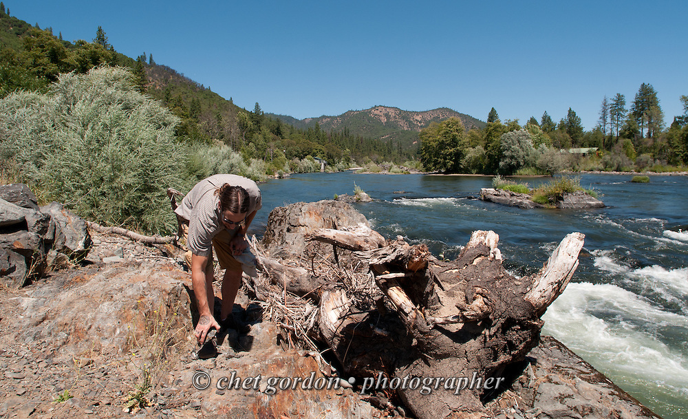 A man examines a handful of sediment for gold flakes along the banks of the Rogue River in Gold Hill, OR on Sunday, July 24, 2016.  © Chet Gordon • Photographer