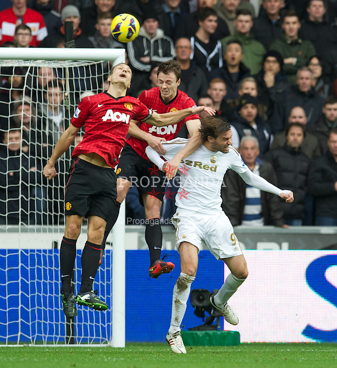 SWANSEA, WALES - Sunday, December 23, 2012: Manchester United's Nemanja Vidic and Jonny Evans in action against Swansea City's Miguel Perez Cuesta 'Michu' during the Premiership match at the Liberty Stadium. (Pic by David Rawcliffe/Propaganda)