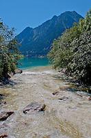 River rushing into the beautiful blue lake at La Prese in Graubunden, Switzerland.