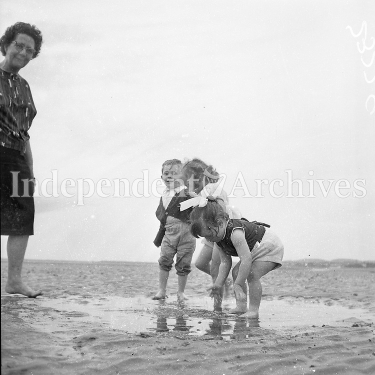 Children play in the water on the sand. Names, date and location unknown.<br />