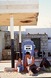 cowboy and little boy enjoying time together by an old gas station