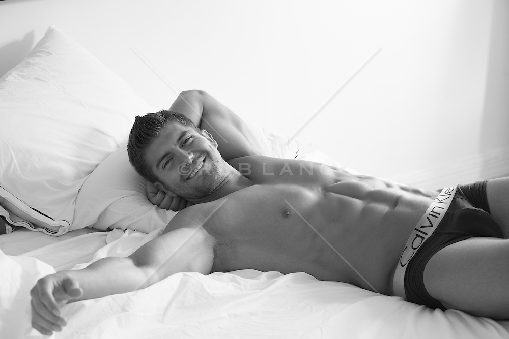 sexy man relaxing in bed wearing briefs