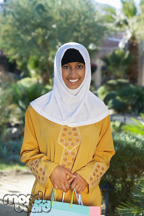 Portrait of young muslim woman with shopping bag, smiling