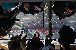 © Licensed to London News Pictures. 23/04/2017. LONDON, UK.  Visitors photograph marathon runners, seen from the glass walkway of Tower Bridge, as runners reach the half way point.  Photo credit: Vickie Flores/LNP