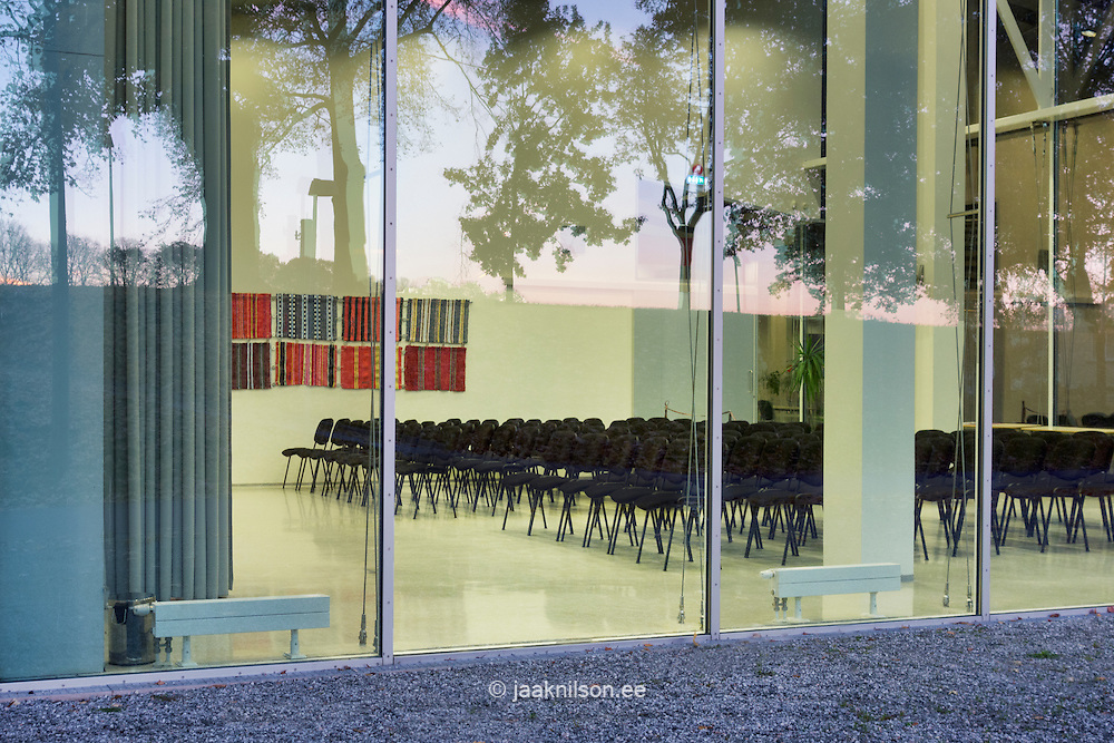Conference, meeting room in Pärnu public library, Estonia. Windows and chairs in lighted lecture room. Reflection on glass wall.