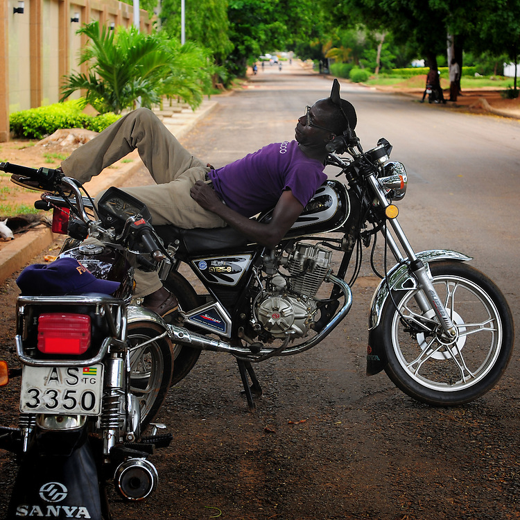 12-05-29   - LOME, TOGO -    A zemidjan ('take me quickly' in  Fon) driver demonstrates how he sleeps on his motorcycle in Lomé, Togo on May 29. Underpaid, rarely thanked and working all hours to make a meagre living, they find very few moments of calm and quiet in their lives. And so, the moto-taxi men have perfected various ways of calmly sleeping on their motorbike as they wait for  their next customer. And so, on the move amidst the chaos and bustle of daily life, they relax and sleep.  Photo by Daniel Hayduk